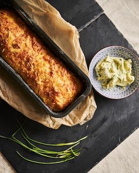 허브와 함께 나무 접시에 허브 버터와 치즈 빵 덩어리