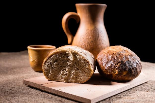 手作りの彫刻が施された木製のピッチャーとバックグラウンドで飲むカップとテーブルの上の木製のまな板の上で半分に分割された焼きたての職人の全粒粉パンの塊