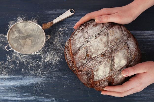 色の木製テーブルの上の女性の手で焼きたてのパンの塊
