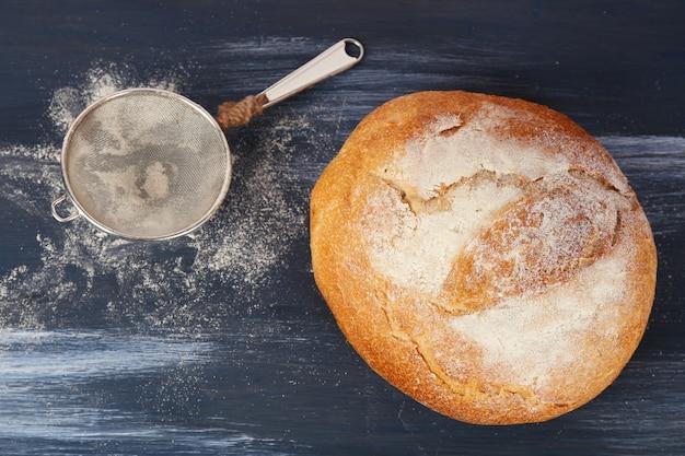 色の木製テーブルに小麦粉のストレーナーと焼きたてのパンの塊
