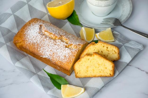 Буханка лимонного торта без глютена с сахарной пудрой, кусочками лимона и чашкой на кухонном полотенце на мраморном столе. закройте кусочек цитрусового пирога по классическому рецепту. здоровое питание, домашний веганский десерт.