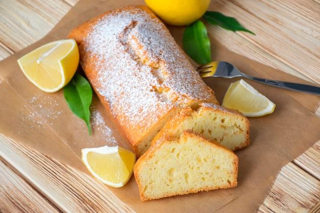 Буханка лимонного торта без глютена с сахарной пудрой, кусочками лимона, зелеными листьями на деревенском деревянном фоне. закройте кусочек цитрусового пирога по классическому рецепту. здоровое питание, домашний веганский десерт.
