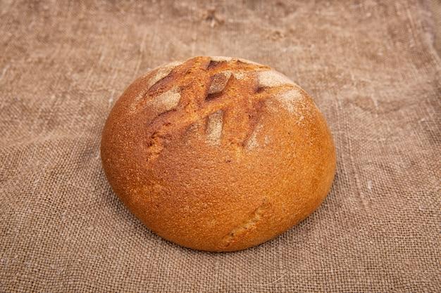 黄麻布のクローズアップと素朴な木製のテーブルのライ麦パン