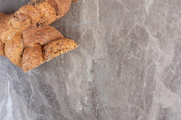 Буханка хлеба струча, разрезанная пополам на мраморе.
