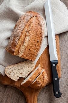 Буханка цельнозернового хлеба с ломтиками на деревянной доске на кухонном столе
