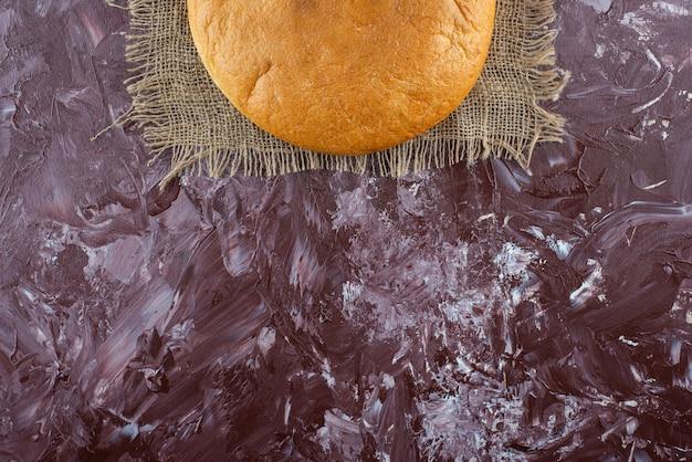 Una pagnotta di pane tondo con una crosta su una tela di sacco.