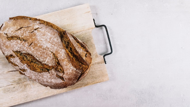 Loaf of rustic baked bread on chopping board over white background