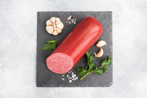 A loaf of salami servelat sausage on a cutting board with parsley and spices and garlic. top view