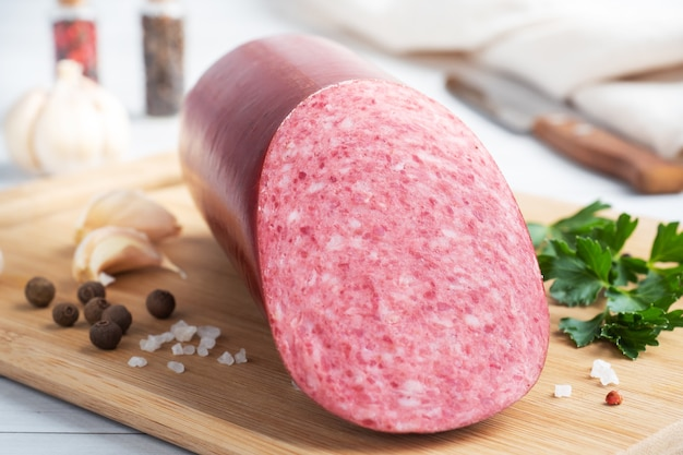 A loaf of salami servelat sausage on a cutting board with parsley and spices and garlic.