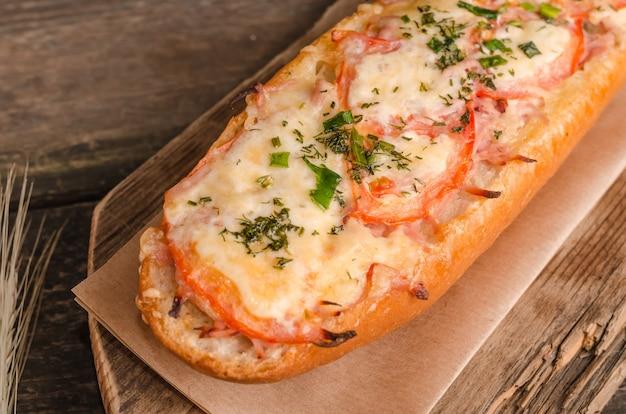 チーズとトマトを詰めたパンは、木製の背景に選択的に焦点を当ててクローズアップ