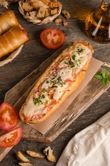 木製の背景にチーズとトマトを詰めたパン、食材、ファーストフード