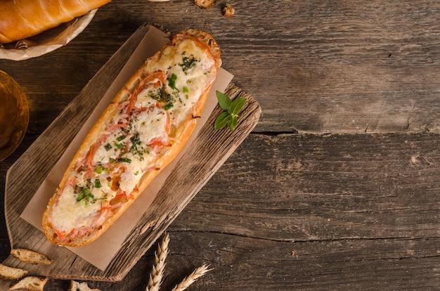 コピースペースのある食材と木製の背景にチーズとトマトを詰めたパン
