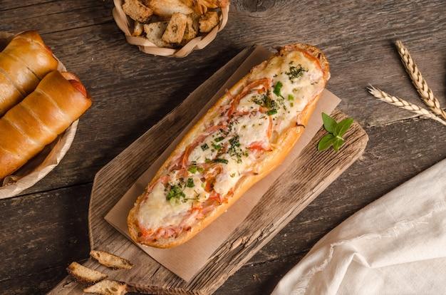材料と木製の背景にチーズとトマトを詰めたパン
