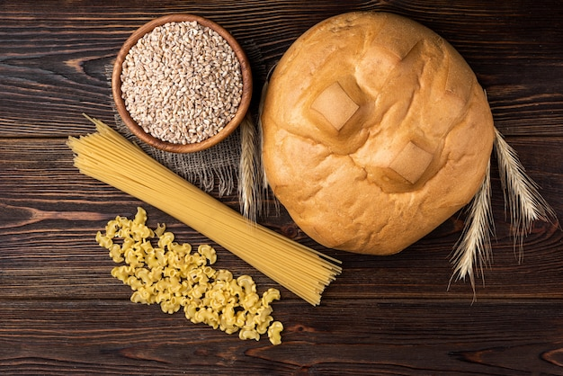 Loaf, wheat and pasta on dark wooden background