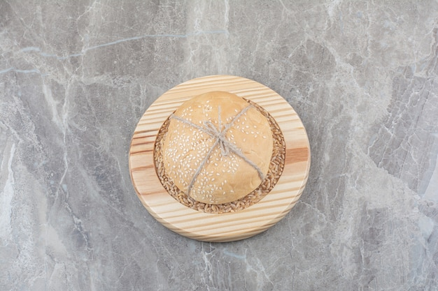 Una pagnotta di pane bianco con chicchi di avena su tavola di legno