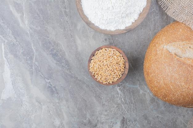 Una pagnotta di pane bianco con chicchi di avena e farina su superficie di marmo