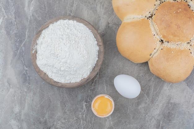 Una pagnotta di pane bianco con tuorlo e farina su tavola di legno