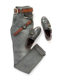 Модная концепция, одежда людей установила с ботинком loafer, джинсы, вахта и пояс изолированные на белой предпосылке. вид сверху