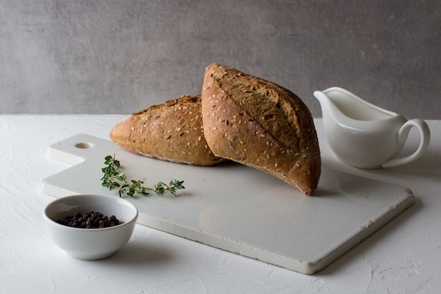 Loafs of whole grain bread on white rustic ceramic cutting board.