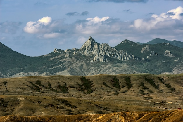 Loamy terrain with gullies and ravines without vegetation, and rocky mountains on the horizon Premium Photo