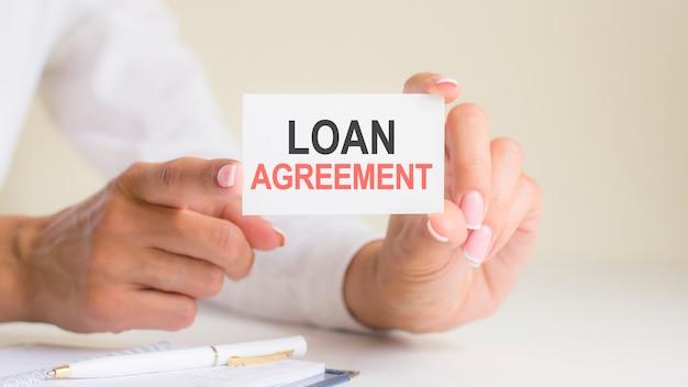 Кредитное соглашение слова надпись на листе бумаги белой карты в руках женщины. черные и красные буквы на белой бумаге. бизнес-концепция, серый фон