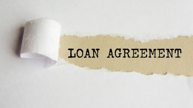 Loan agreement. words. text on gray paper on torn paper background.