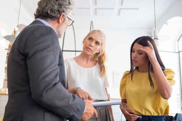 Ispettore di prestito con riunione sul blocco note con giovani imprenditori in loco