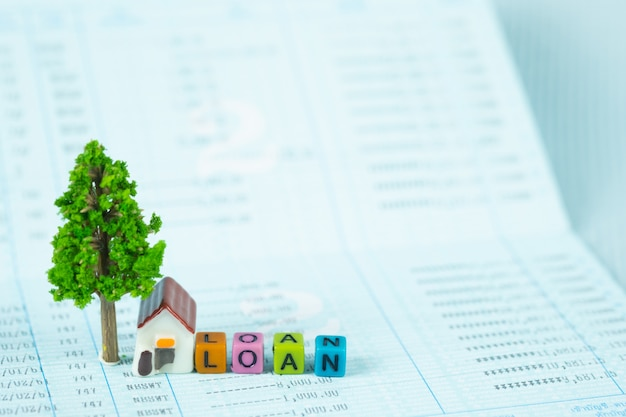 Loan text and small model house and little tree with notebook