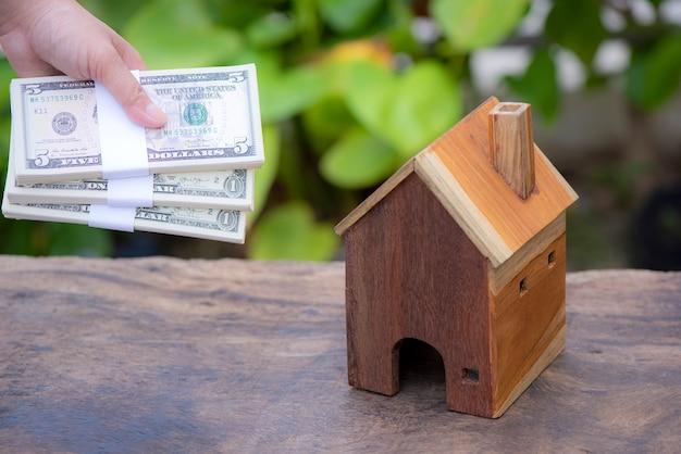 부동산 개념 손에 대 한 대출 공공 공원에 넣어 돈과 모델 홈을 들고