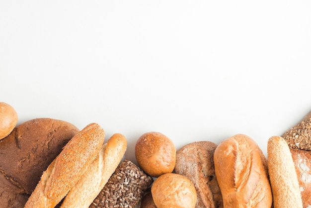 Loaves of baked breads on white backdrop