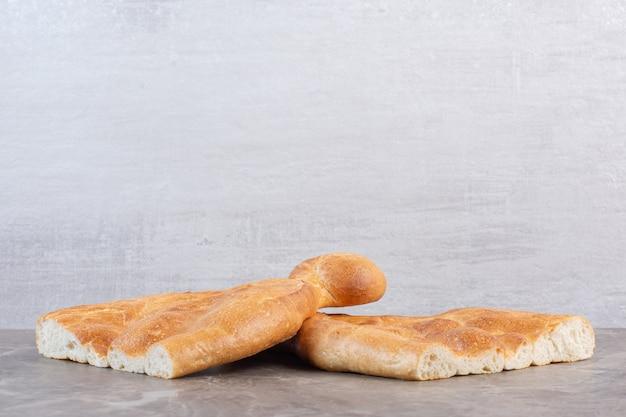 Буханки полурезанного хлеба тандури на мраморе.