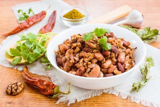 Lobio - the national georgian dish of beans in a white plate and the ingredients for its preparation on a wooden table