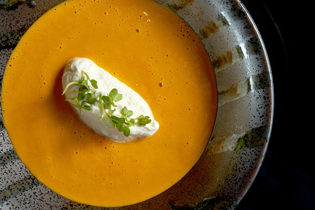 Lobster cream soup with cream cheese in a black bowl isolated on a black background.