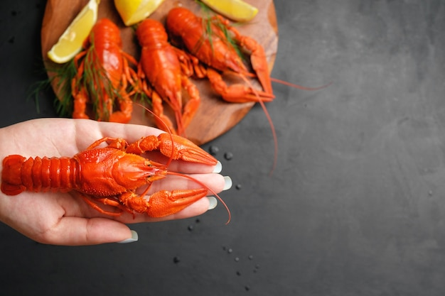 Lobster in hand of woman, lobsters with lemon lime on black background top view