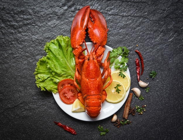 Lobster on plate seafood shellfish shrimp with lemon salad lettuce vegetable and tomato
