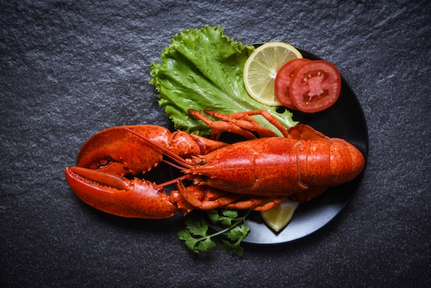 Lobster on plate seafood with lemon salad lettuce vegetable and tomato