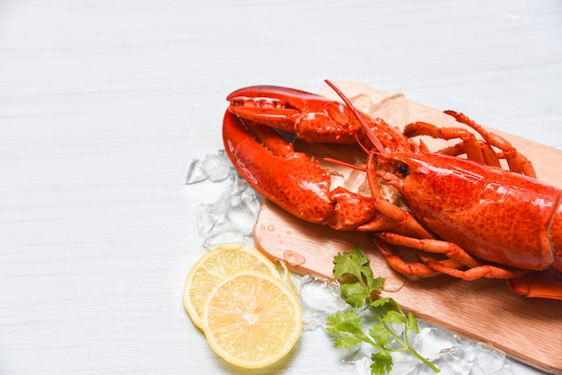 Lobster seafood with ice  on wooden cutting board and lemon coriander / close up of steamed lobster food