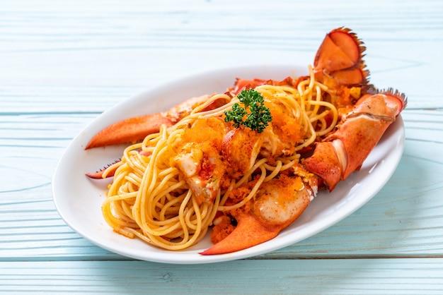 Спагетти с лобстером и яйцом из креветок на белой тарелке
