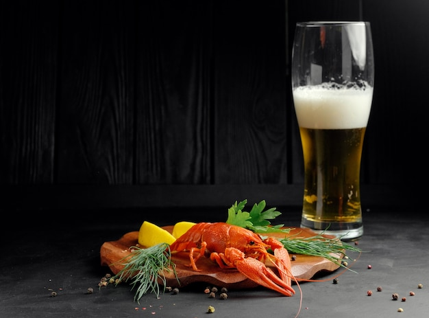 Лобстер с пивом, лимоном, лаймом и сухим перцем на черном фоне