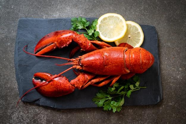 Lobster with vegetable and lemon on black slate plate
