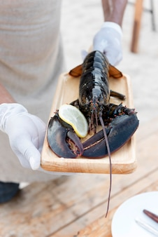 Lobster in wooden plate holding by hand