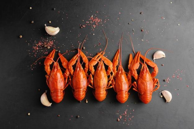 黒の背景の上面図にニンニクと乾燥唐辛子とロブスター
