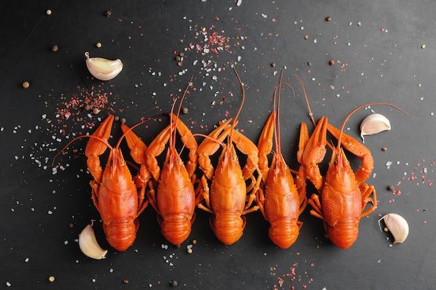 黒の背景の上面図にニンニクと乾燥唐辛子とアカザエビ