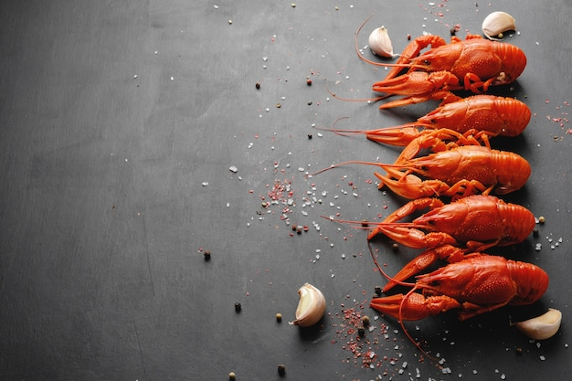 Lobsters with garlic and dry pepper on black background top view