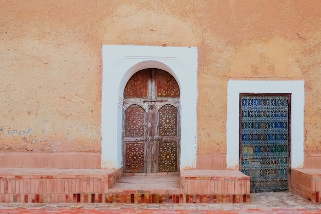 Local antique moroccan pattern carved wooden doors against old orange pink wall