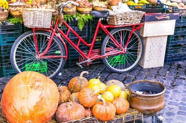 ローマのカンポディフィオーリにある古い自転車とカボチャのある地元の果物市場