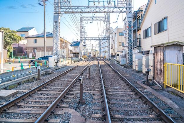 옆에 집과 주차장이있는 일본 현지 철도 트랙