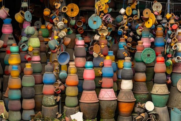 지역 시장. 밧줄에 매달려 있는 작은 점토 기념품, 서로 가까이에 서 있는 밝은 냄비