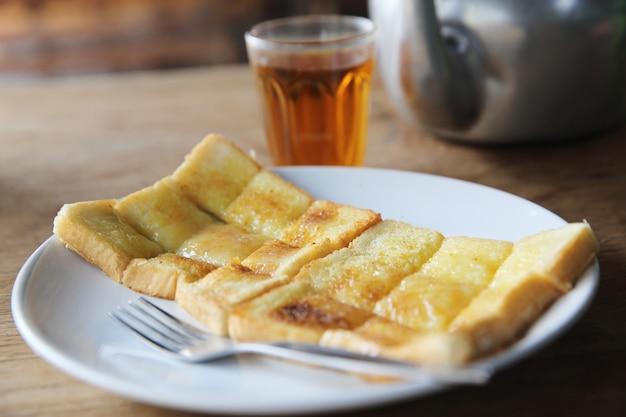 地元の朝のタイ料理のホットティー、半熟卵、トースト