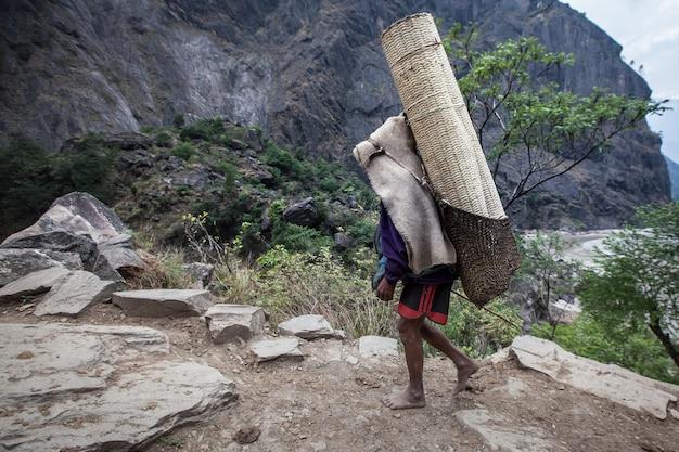 ネパールの山の小道に貨物を運ぶ地元のポーター